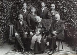siedzą od lewej: Kuba Lewicki, biskup Bandurski, Wiktor Legeżyński senior, stoją od lewej: Wiktor, Maria z Michalskich, Michał Legeżyńscy, oficer